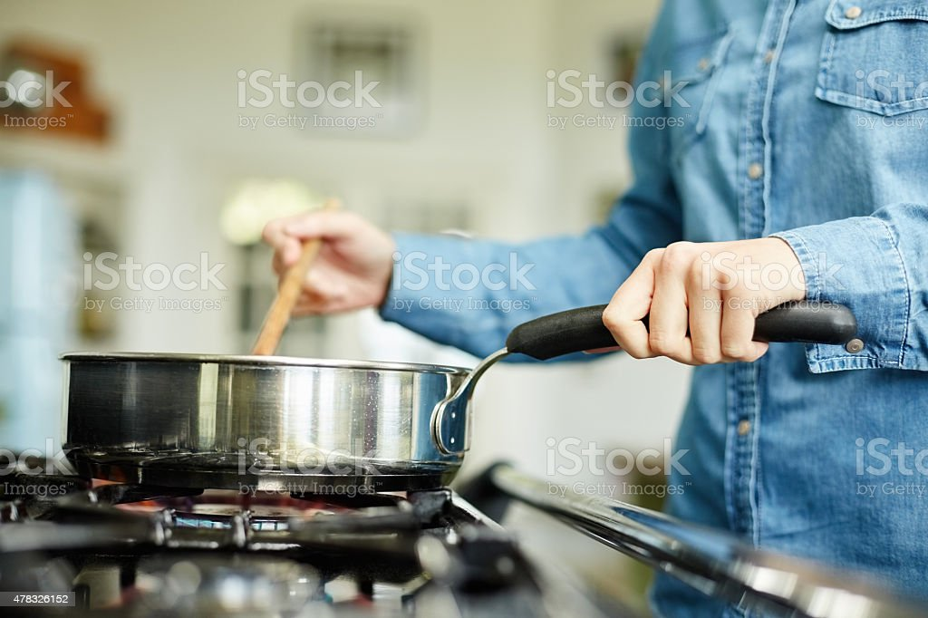 Midsection of woman cooking food in frying pan stock photo