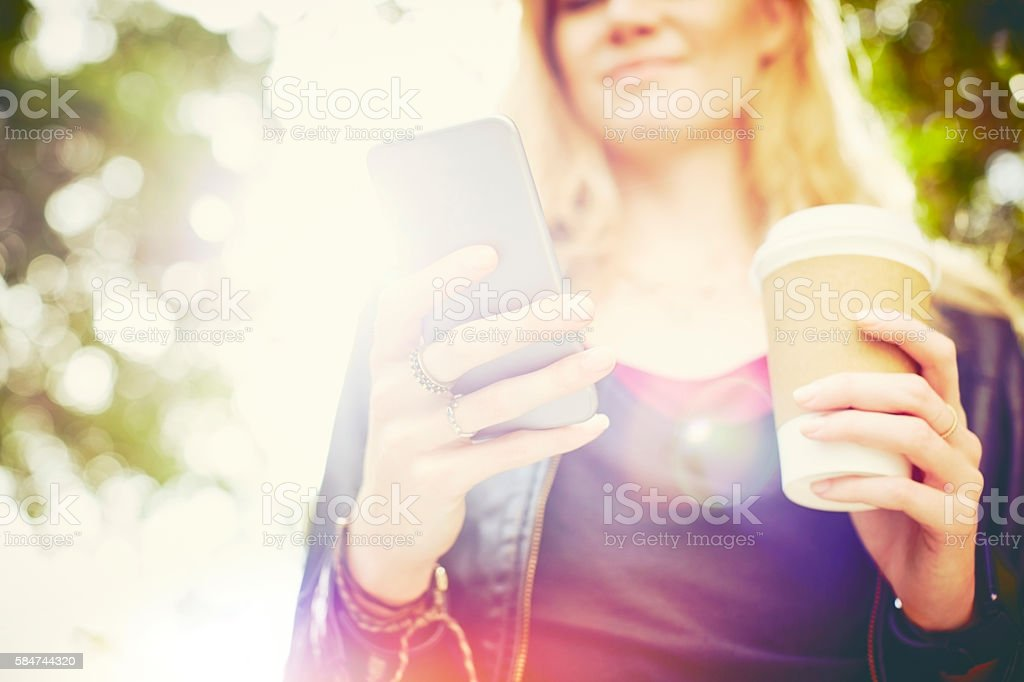 Midsection of woman with smart phone and disposable coffee cup stock photo