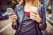 Midsection of woman with smart phone and disposable coffee cup