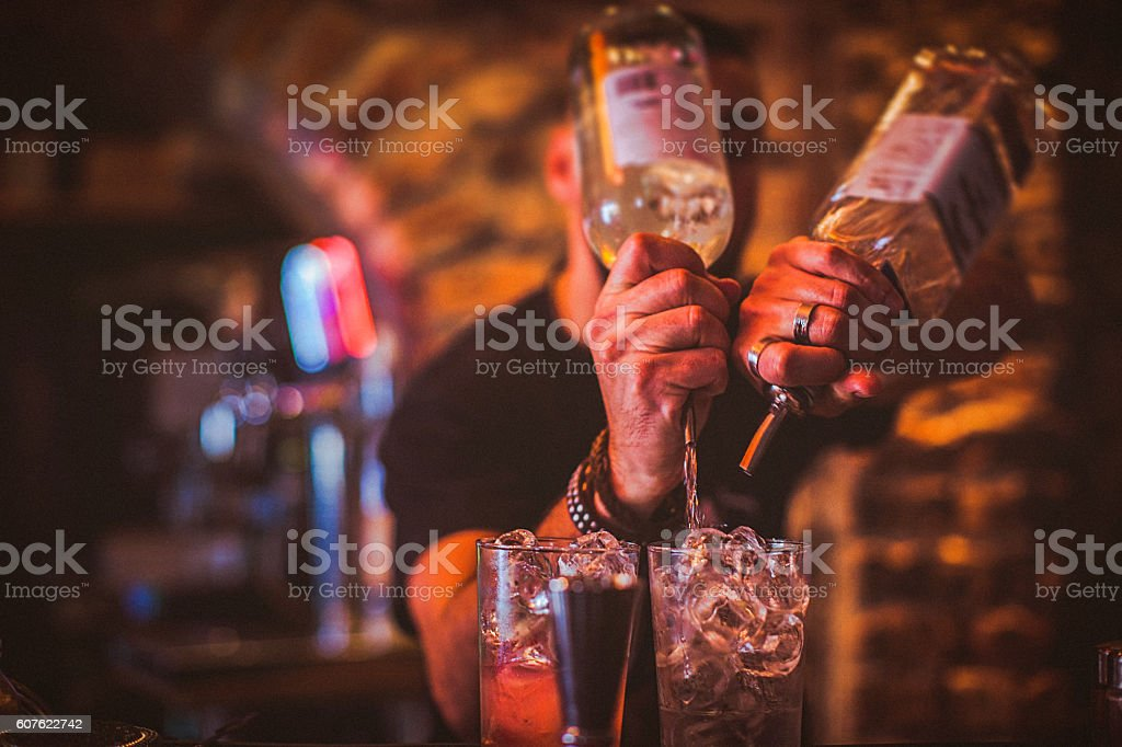 Midsection of young bartender preparing cocktails in nightlife bar stock photo