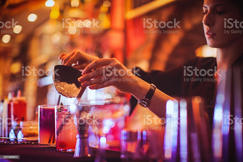 Midsection of young female bartender preparing cocktails in cocktail bar stock photo