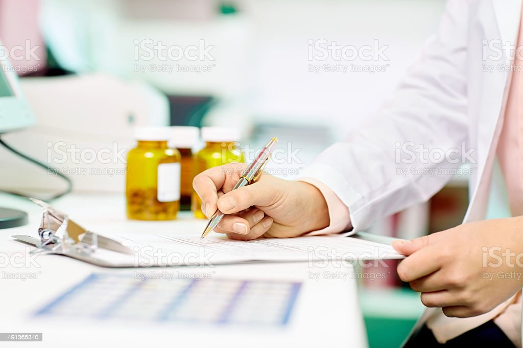 Midsection pharmacist writing on clipboard at desk stock photo