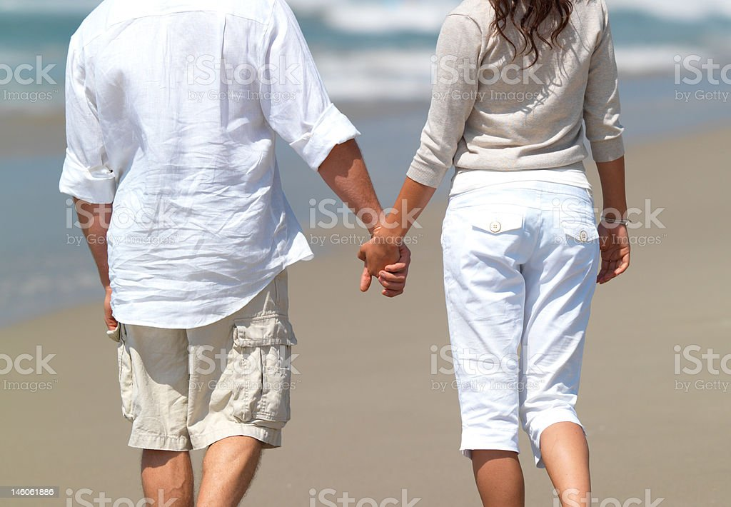 Midsection view of couple walking with holding hands on beach royalty-free stock photo