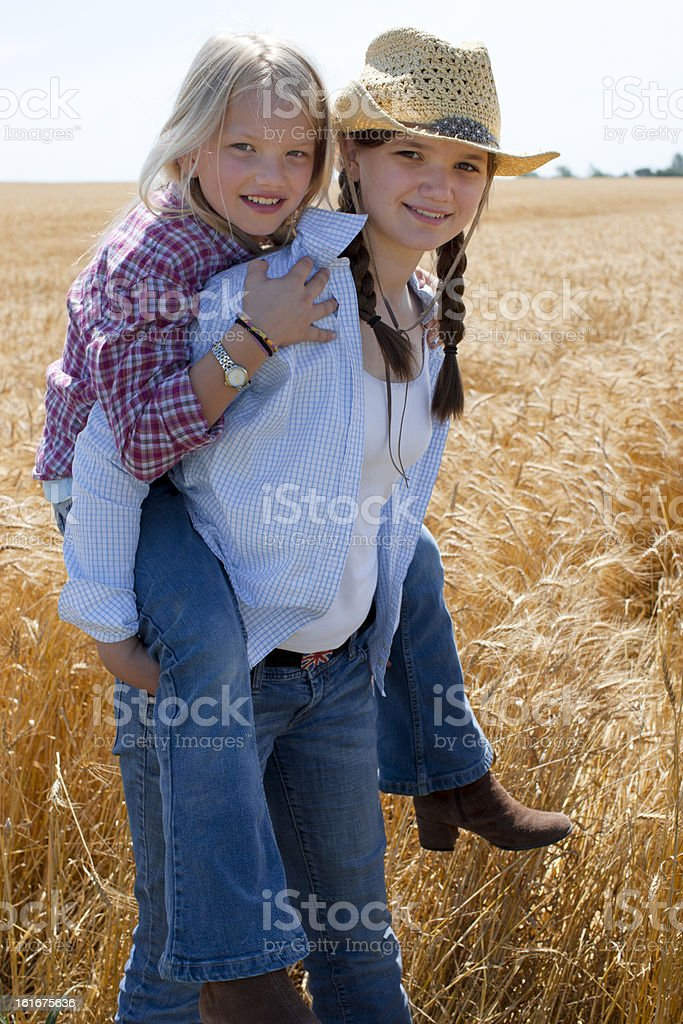 MIdwestern Cowgirl Sisters Play Piggyback in Wheat Field Farm stock photo