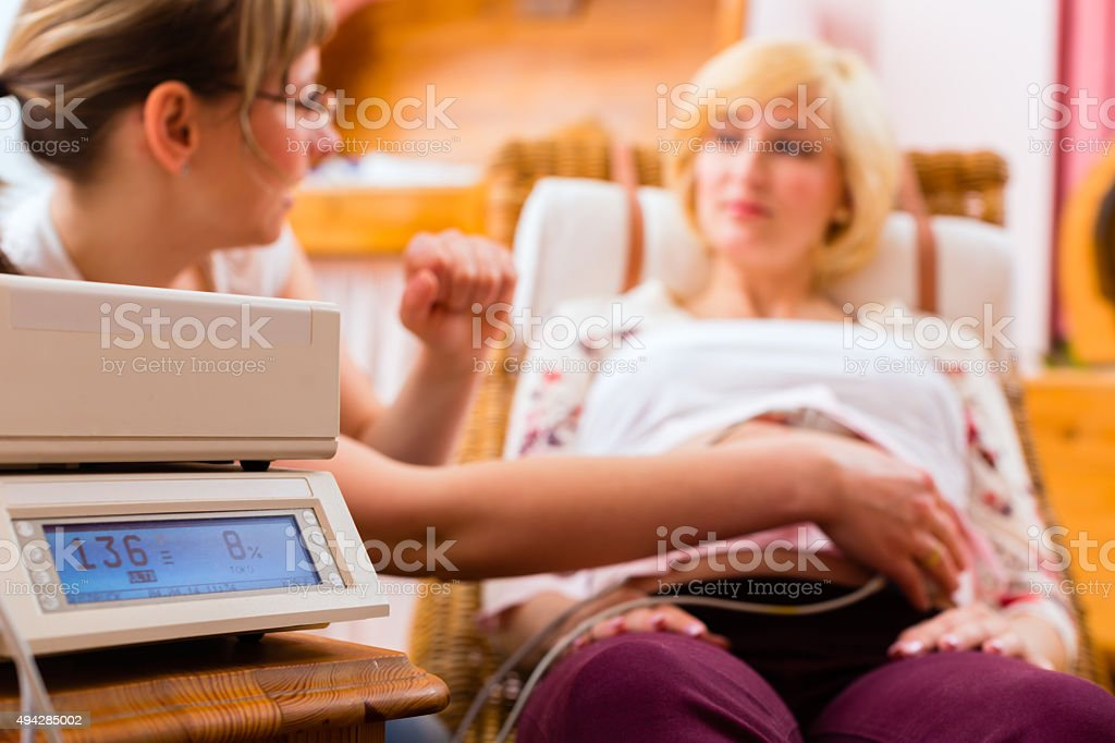 Midwife seeing mother for pregnancy examination stock photo