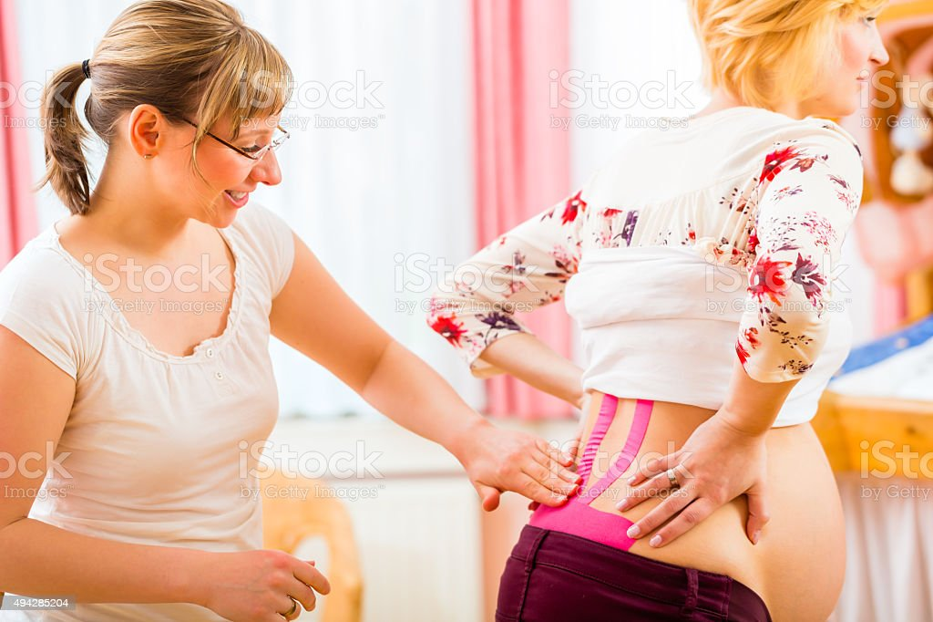 Midwife taping pregnant woman with Kinesio-Tape stock photo