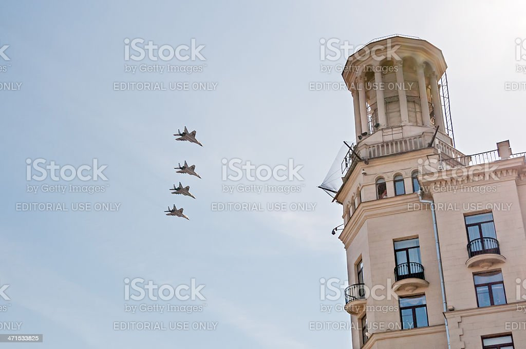 MiG-29 jet fighters fly in rank near building tower royalty-free stock photo
