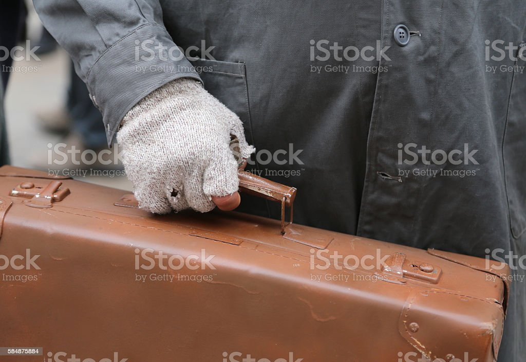 migrant with old leather suitcase and the broken glove stock photo