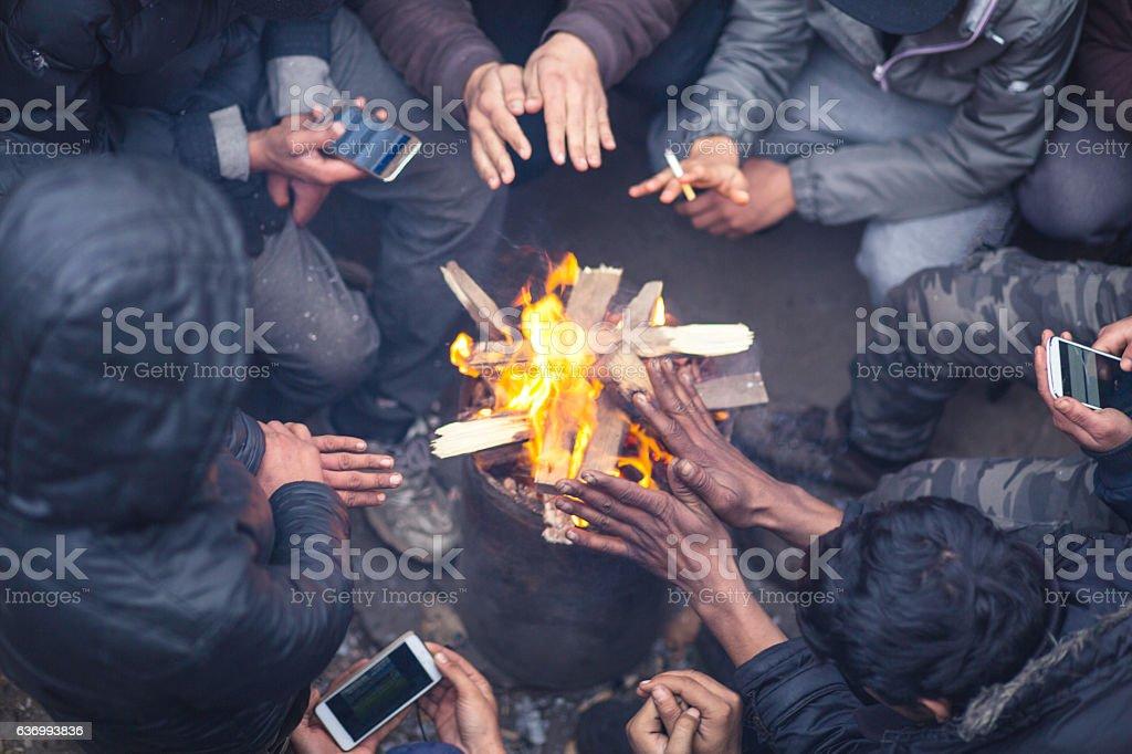 Migrants around the fire. stock photo