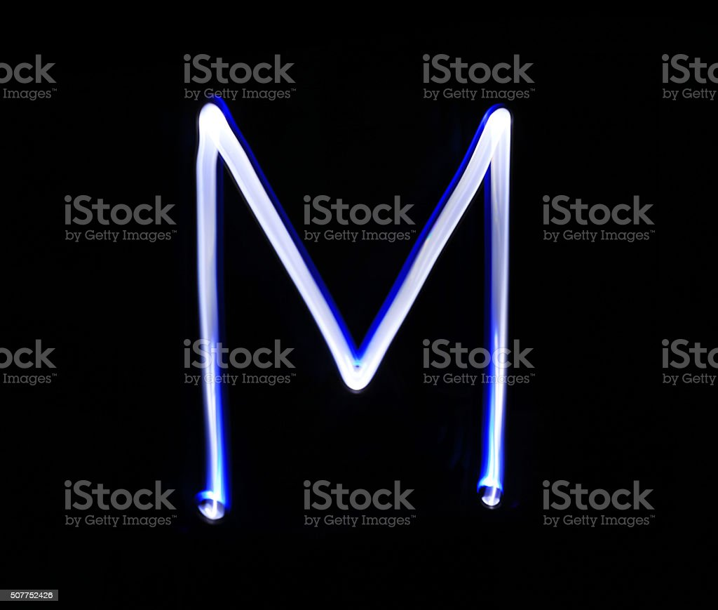 M Mike alphabet hand writing blue light  over black background. stock photo