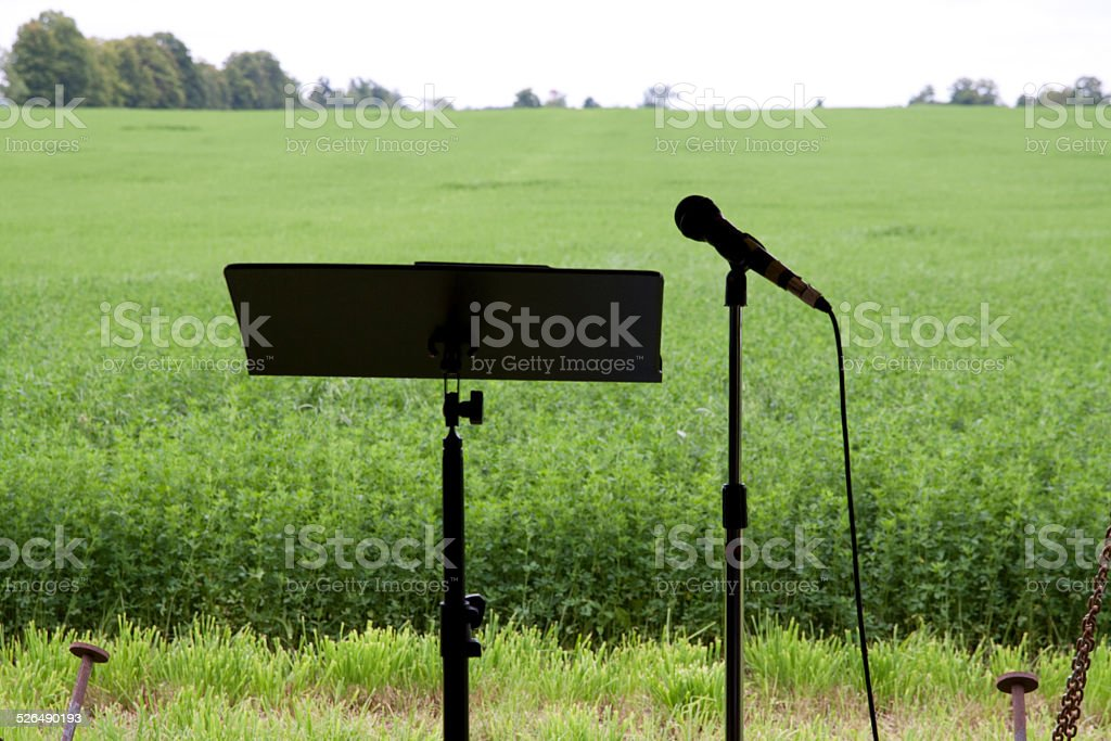 Mike & music stand in field. stock photo