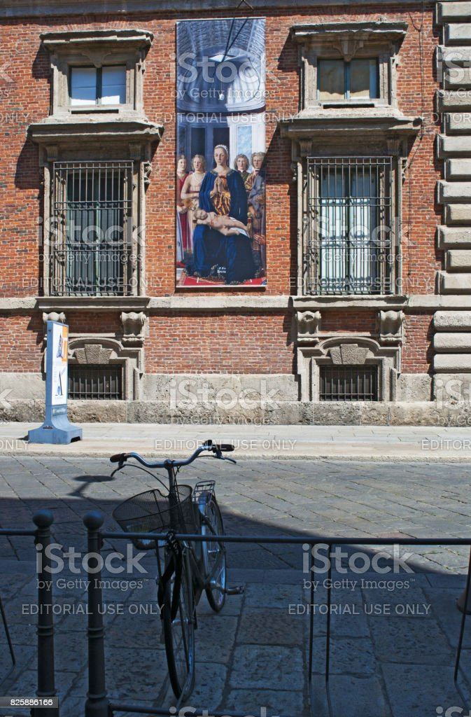 Milan: a bicycle and the poster of the Brera Madonna, painting by Piero della Francesca, on the exterior of Palazzo Brera, palace housing the Pinacoteca di Brera stock photo