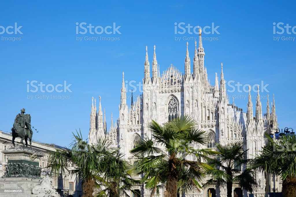 Milan Duomo cathedral with palm trees, blue sky in a sunny day stock photo