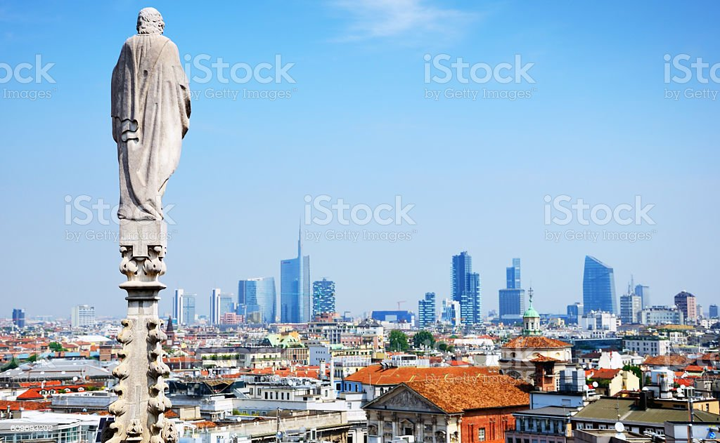 Aerial view of Milan and statue on the roof of Duomo of Milan, Italy
