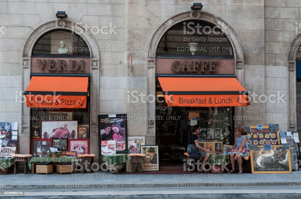 Milan: women seated on a table outside the Caffè Verdi, Verdi Cafe, a well known cafeteria and restaurant near La Scala, or Teatro alla Scala, the most famous opera house in Italy stock photo