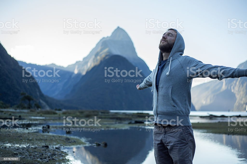 Milford Sound: Young male arms outstretched stock photo