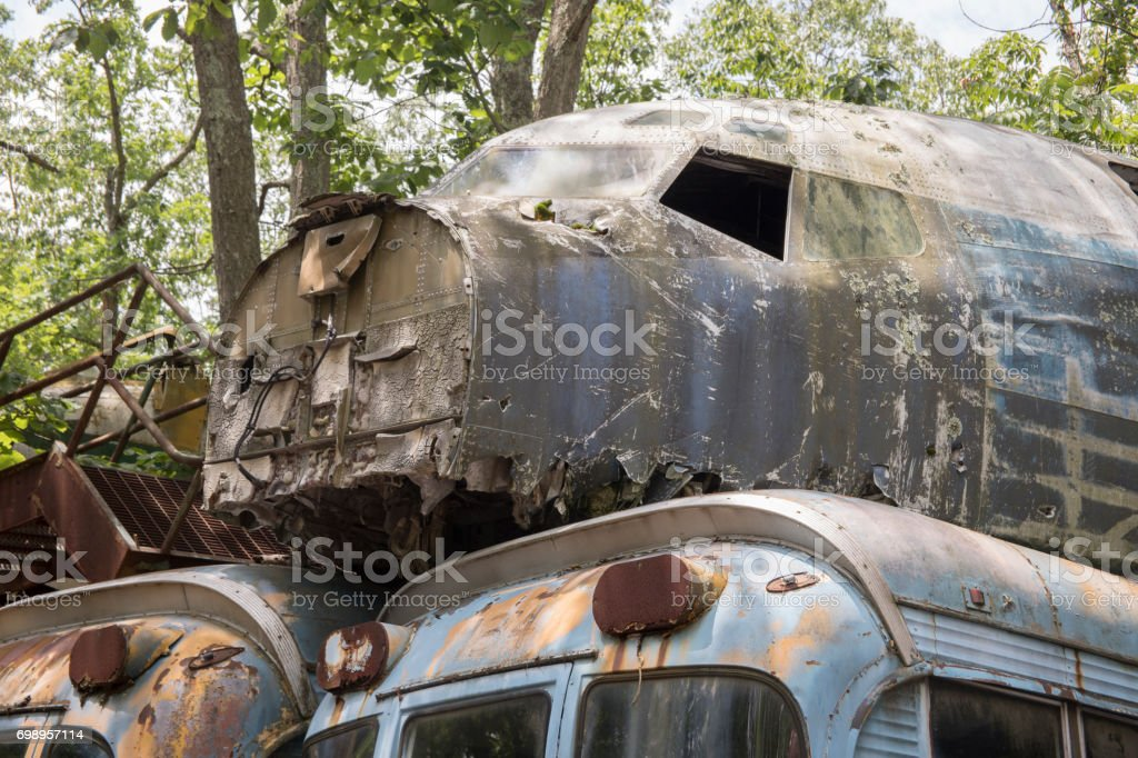 Military aircraft and busses in junkyard stock photo