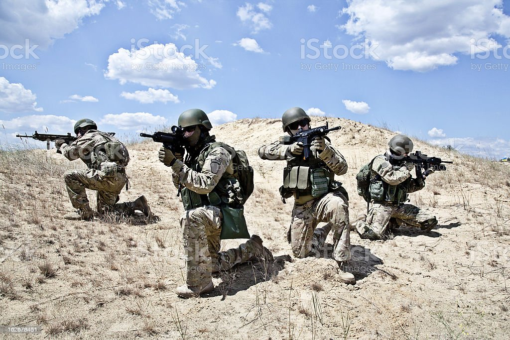 Military army squad on desert aiming stock photo
