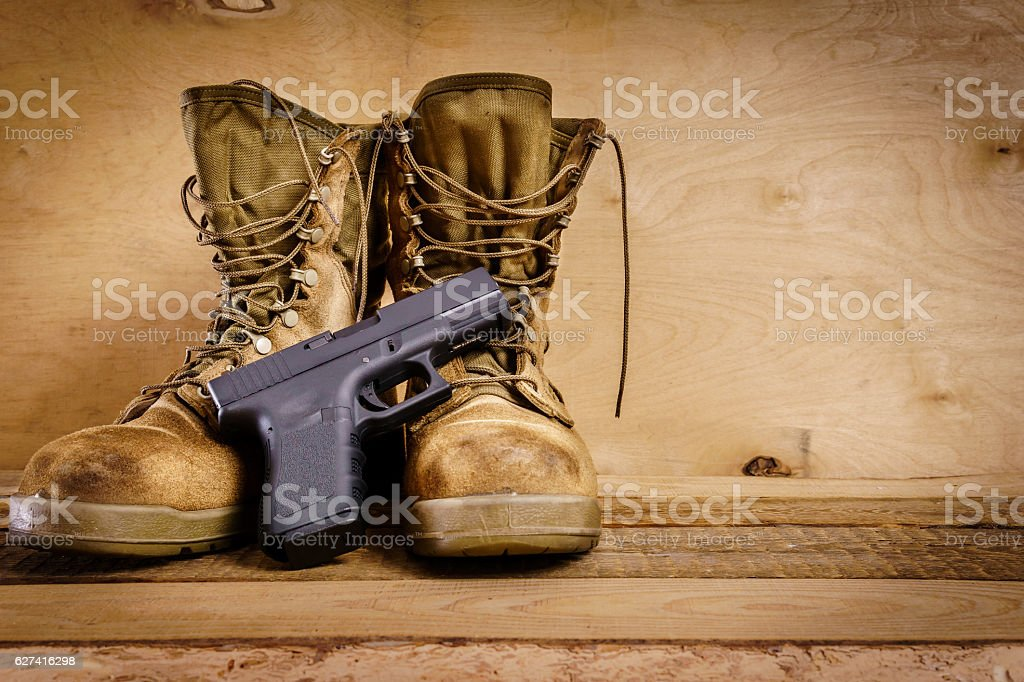 military boots and gun on the table stock photo