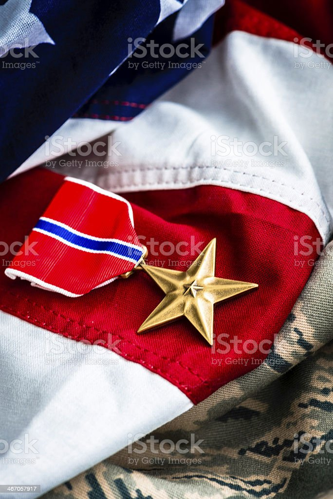 Military Bronze Star Medal on Camouflage Uniform and US Flag stock photo