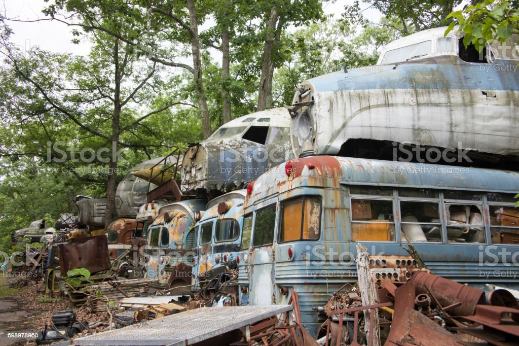 Military buses and aircraft in junkyard stock photo