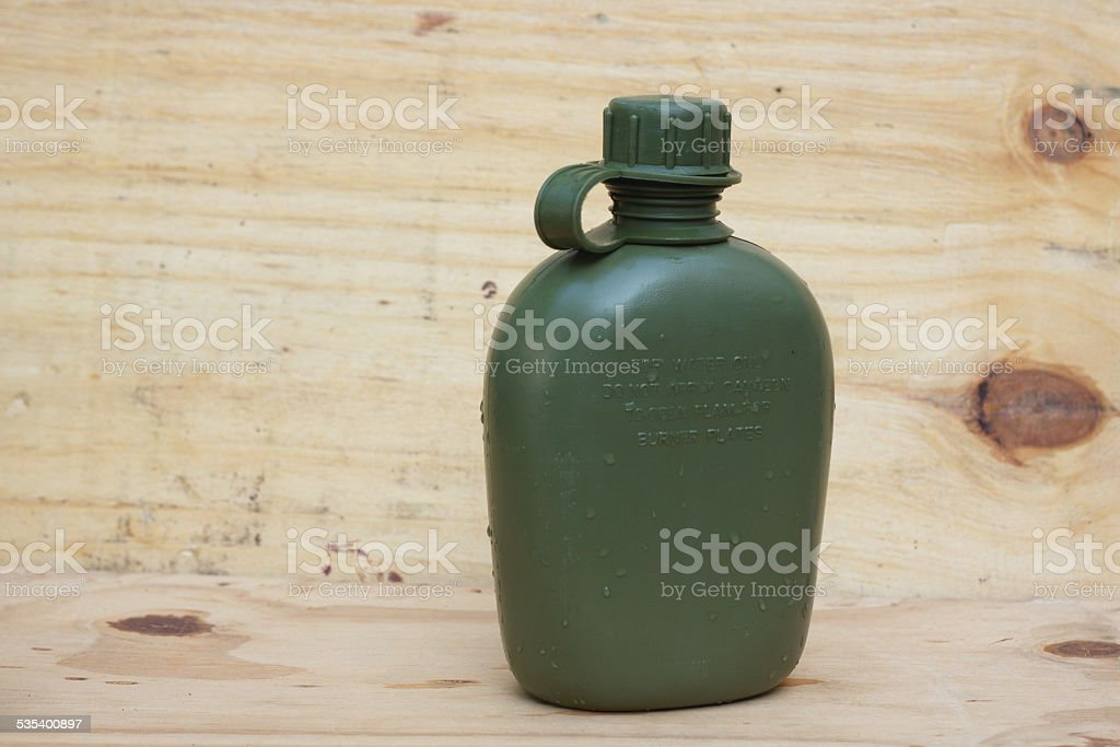 Military canteen on wooden plank stock photo