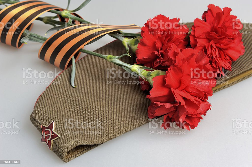 Military cap, carnations tied with Saint George ribbon on gray stock photo