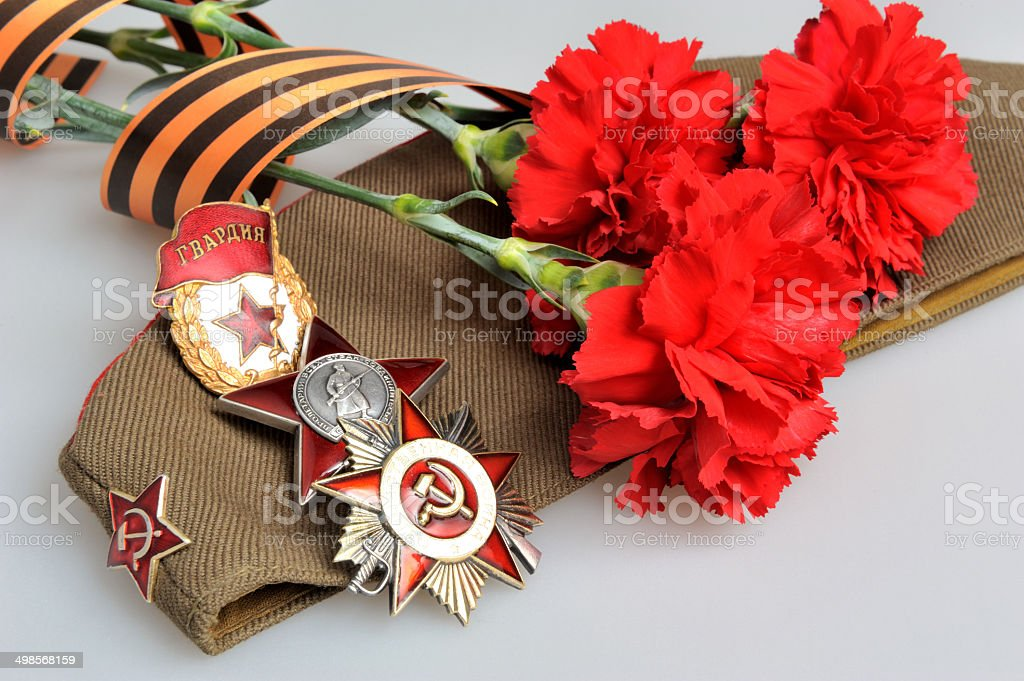 Military cap, red flowers, Saint George ribbon, military orders stock photo