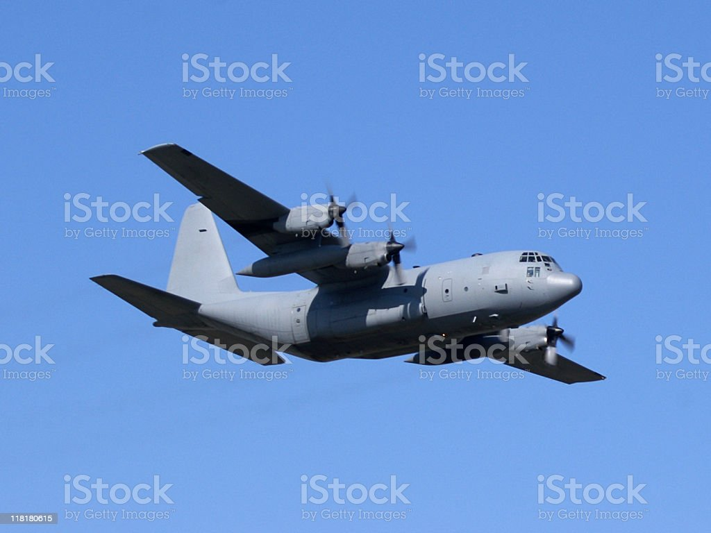 military cargo airplane Lockheed C130 Hercules flying in blue sky stock photo
