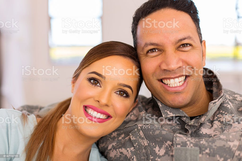 military couple sitting on sofa stock photo
