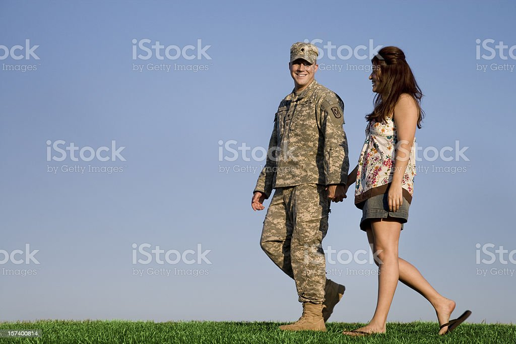 Military couple walks hand in hand on clear sunny day royalty-free stock photo