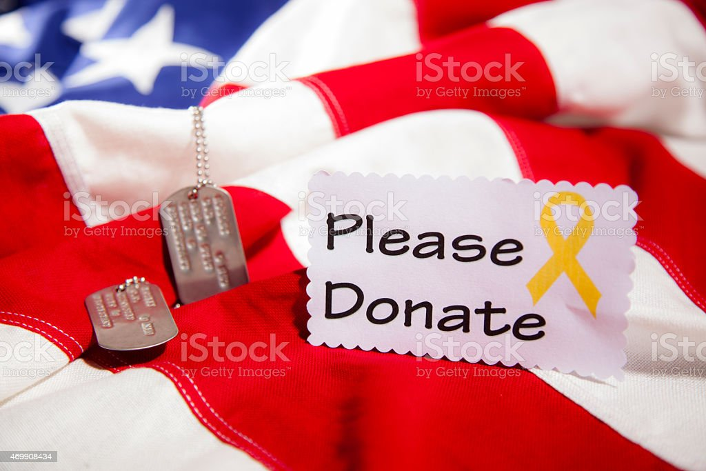Military dog tags beside 'Please Donate' note. American flag. Fundraiser. stock photo
