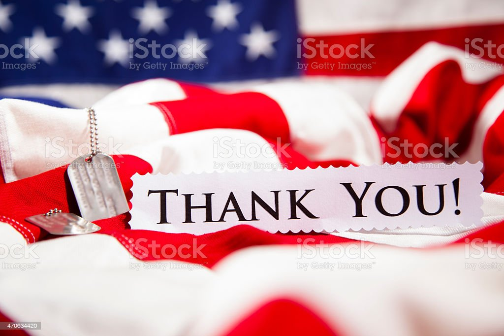 U.S. Military dog tags beside 'Thank You' note. American flags. stock photo