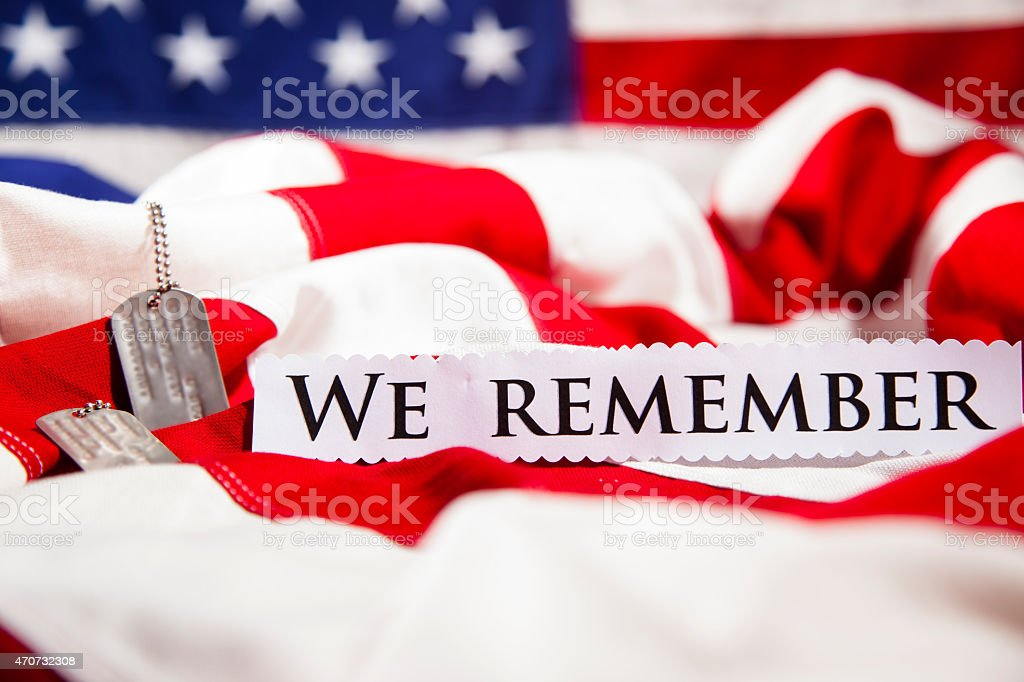 Military dog tags beside We Remember note. American flags. Patriotism. stock photo