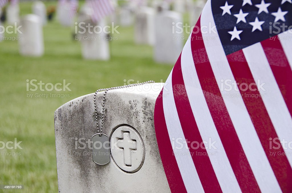 military dog tags on veteran's tombstone stock photo