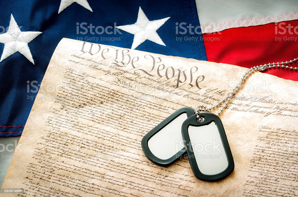 Military dog tags, US constitution and the American flag stock photo