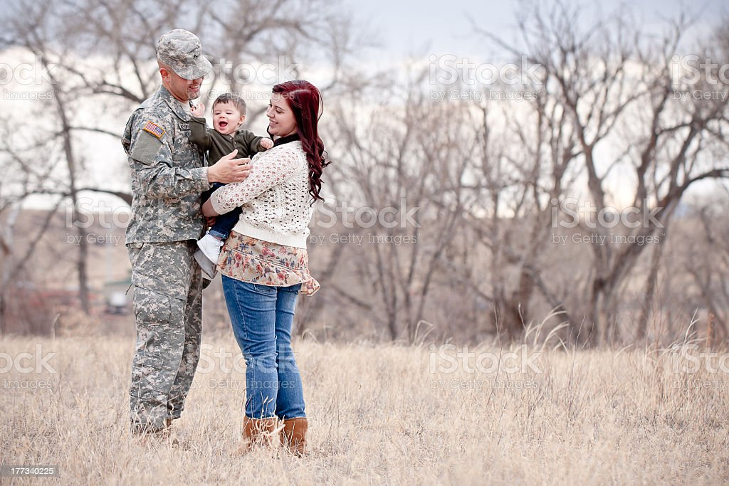 Military family hugging in field stock photo