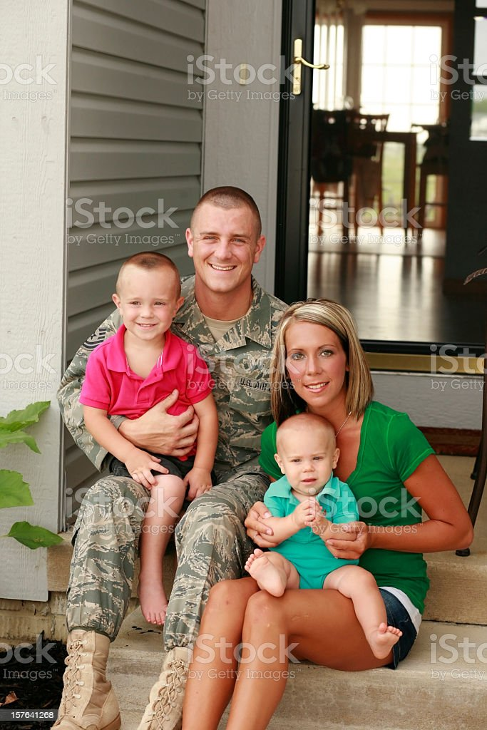 A military family of four sitting out on their front steps stock photo