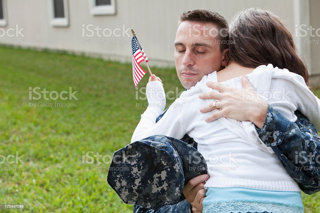 Military father hugging daughter stock photo