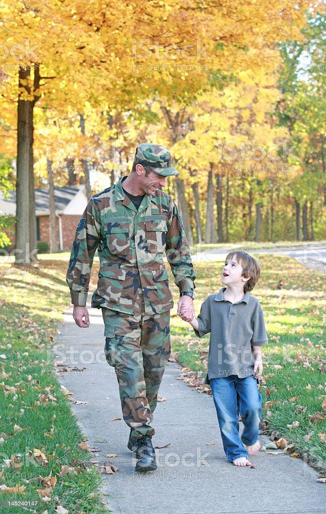 Military Father walking with his son down sidewalk royalty-free stock photo