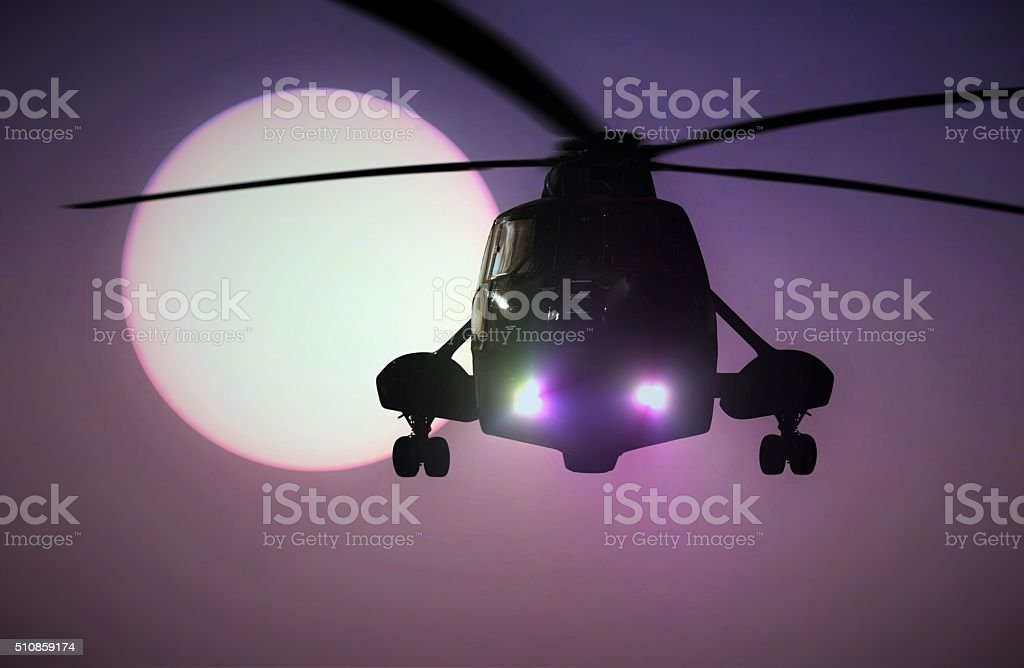 Military Helicopter flying at sunset stock photo