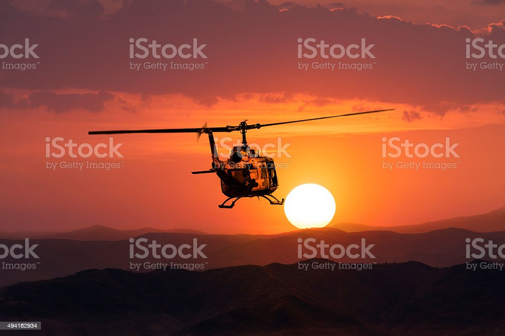 UH-1 Military Helicopter in flight at sunset stock photo