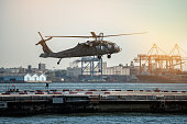 Military helicopter landing on heliport in New York City.