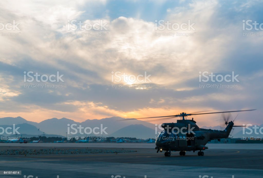 Military helicopter taxiing at dusk stock photo