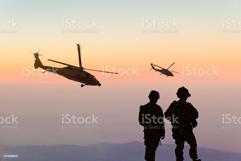 Military Helicopters and Army Soldiers Overlook the Setting Sun stock photo