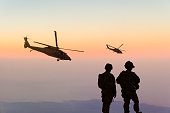 Military Helicopters and Army Soldiers Overlook the Setting Sun