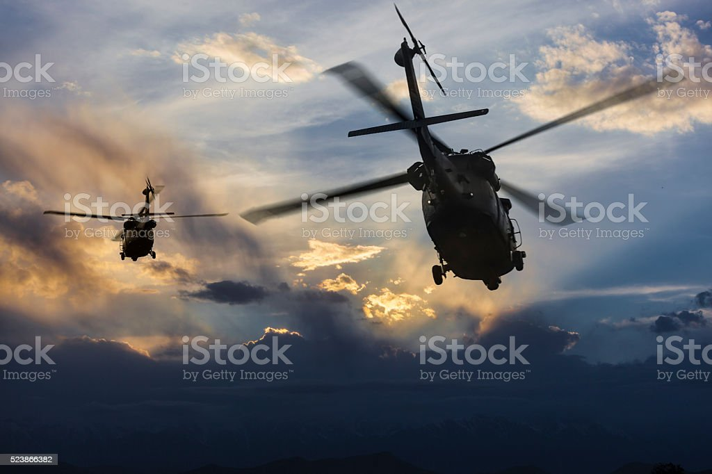 Military Helicopters in flight et sunset stock photo