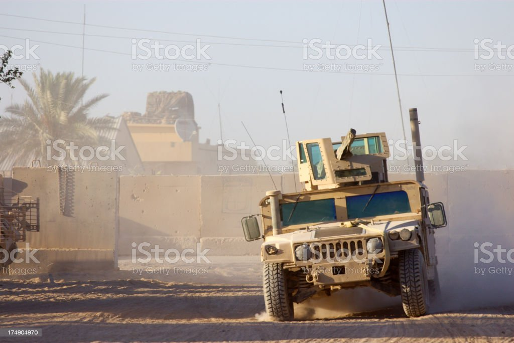 Military humvee driving through desert like conditions stock photo