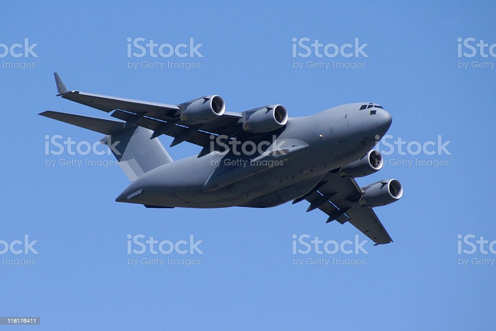 military jet cargo airplane C17 Globemaster flying in blue sky royalty-free stock photo