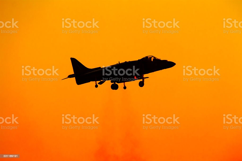 Military jet hoovering and taking off stock photo